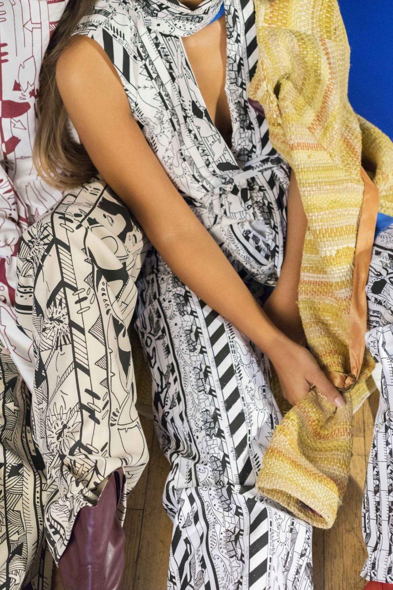 Eine Frau trägt einen schwarz-weißen Einteiler. Über der Schulter liegt der Ärmel eines gestrickten Pullovers.