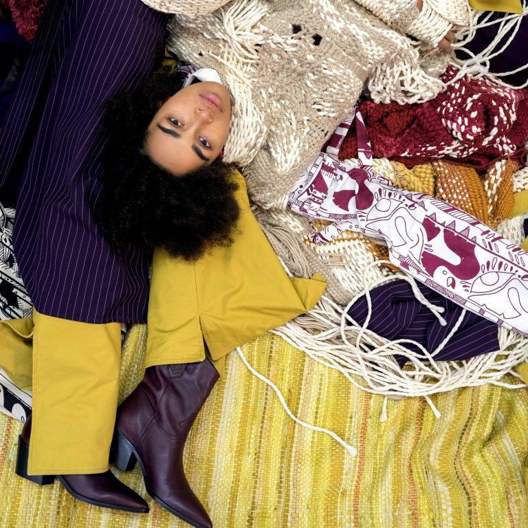 Eine Frau liegt auf dem Boden. Sie trägt einen grob gestrickten Pullunder. Neben ihr auf dem Boden liegen eine Hose und Schuhe.