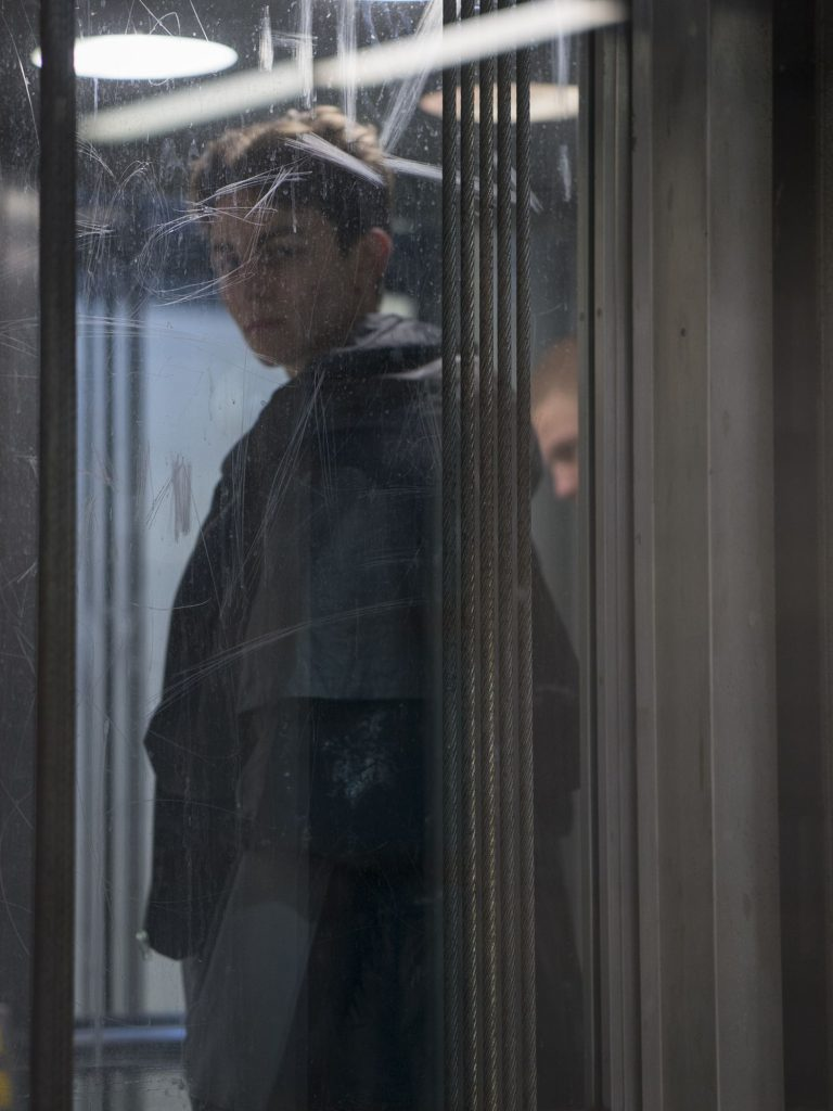 Ein junger Mann steht in einem Aufzug. Er ist nur durch die verkratzte Scheibe zu sehen.