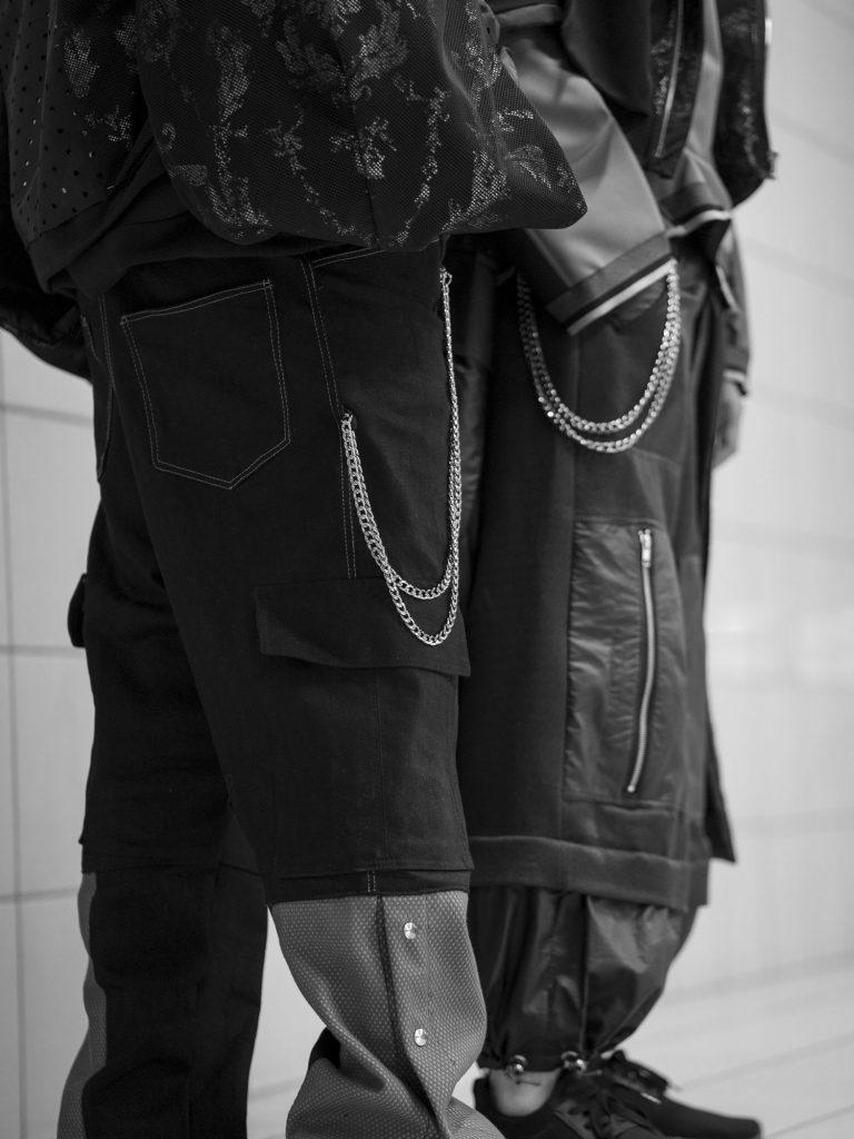 Die Unterkörper zweier junger Männer in breiten Hosen. An den Hosen sind silberne Ketten befestigt.