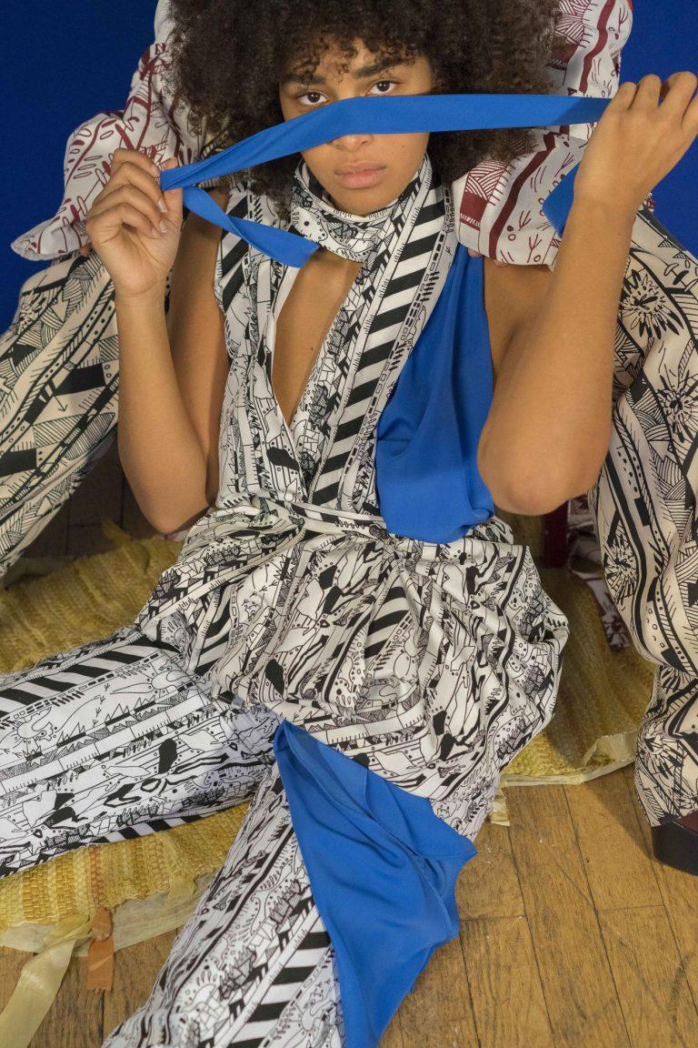 Eine Frau sitzt auf dem Boden. Sie trägt einen schwarz-weißen Einteiler. Vor dem Gesicht und an Brust und Bein ist blauer Stoff eingearbeitet.