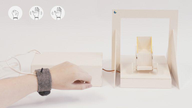 Eine Hand trägt ein Armband, welches mit Kabbeln mit einem kleinen Rollstuhl Modell verbunden ist.