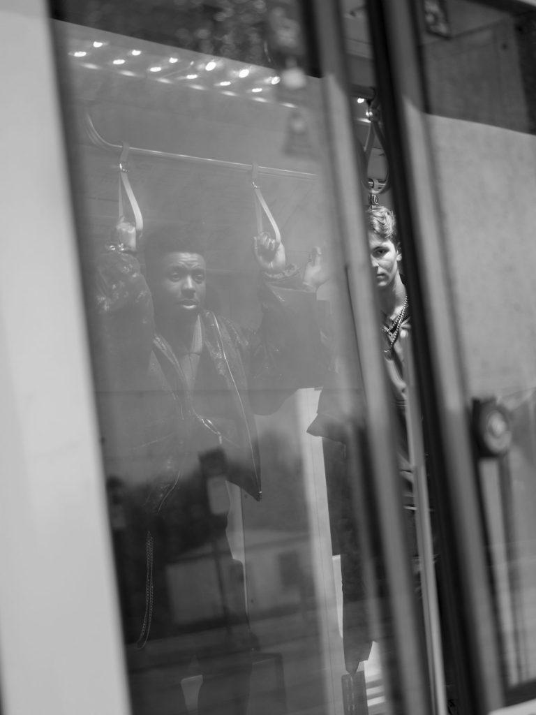 Zwei junge Männer in einer Straßenbahn. Die Männer sind nur als Reflexion auf den Türscheiben zu sehen.