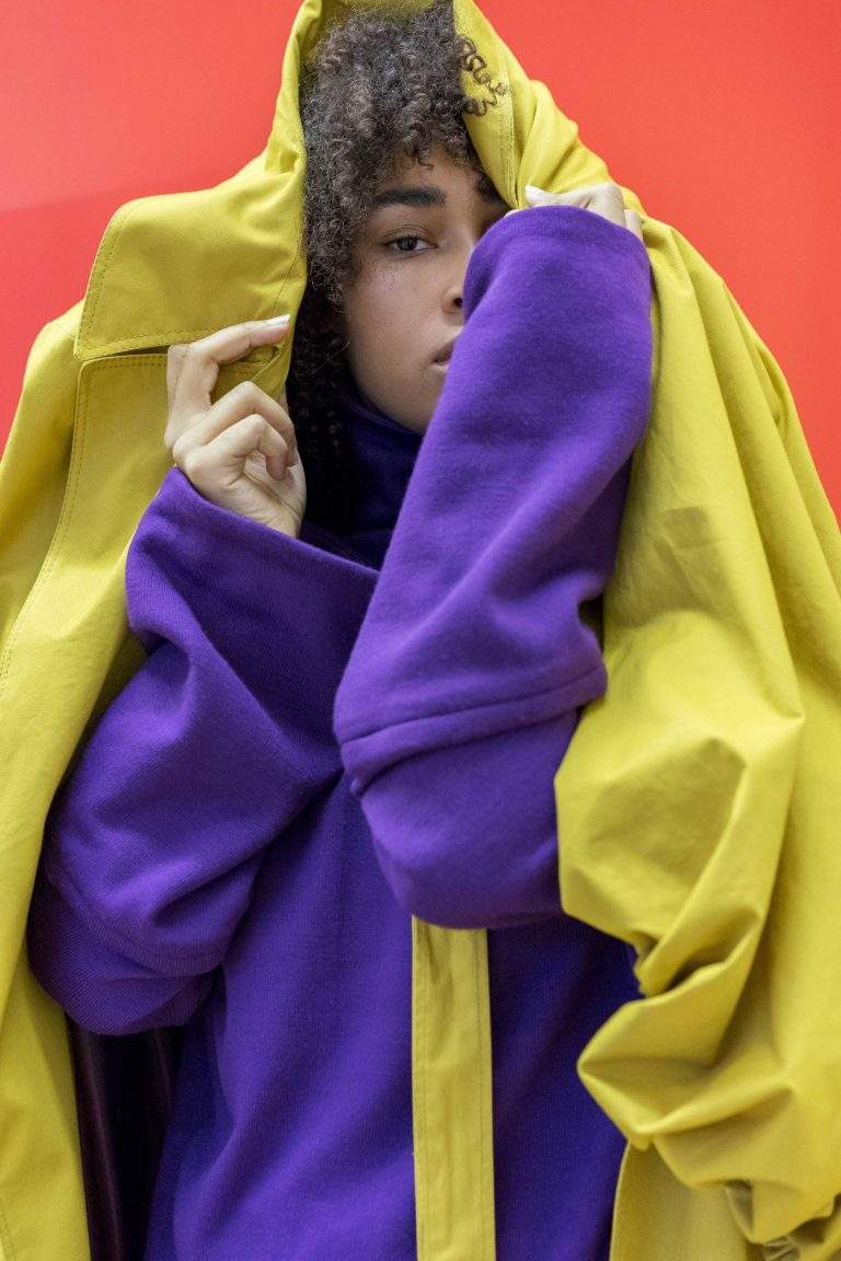 Eine Frau steht vor einem roten Hintergrund. Sie trägt einen blauen Pullover und zieht sich einen gelben Mantel über den Kopf.