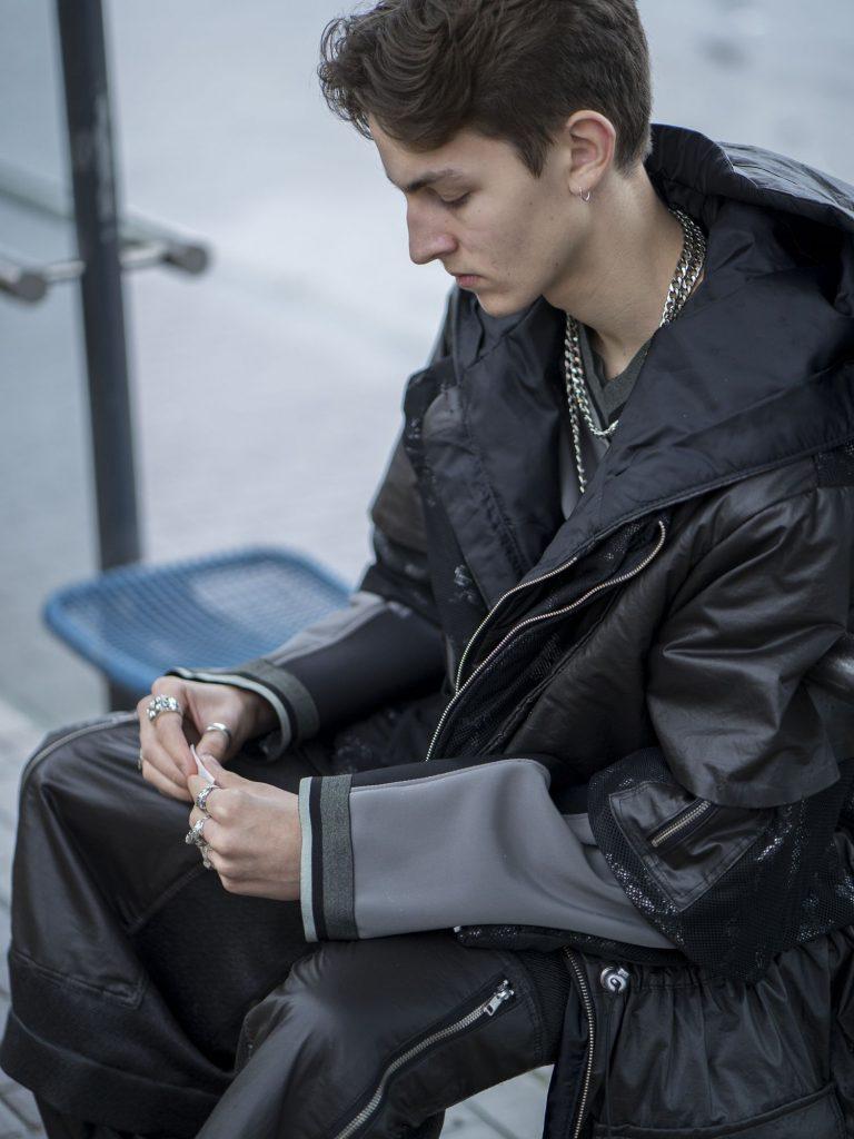 Ein junger Mann in weiter Kleidung sitzt an einer Bushaltestelle und dreht sich eine Zigarette.