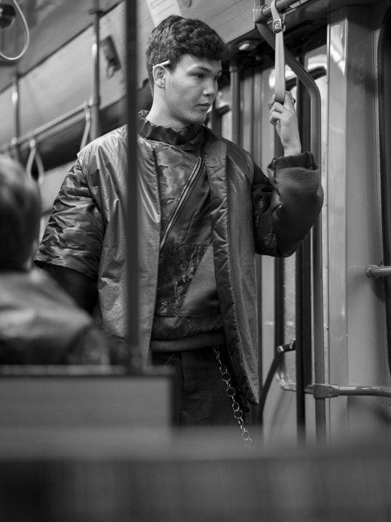 Ein junger Mann mit weiter Kleidung steht in der Straßenbahn. Hinter seinem Ohr steckt eine Zigarette.