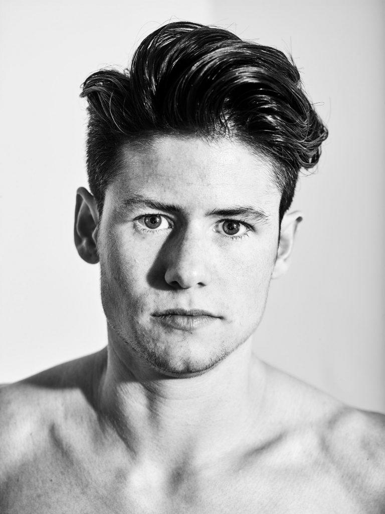 Das Porträt eines jungen Mannes mit nacktem Oberkörper.