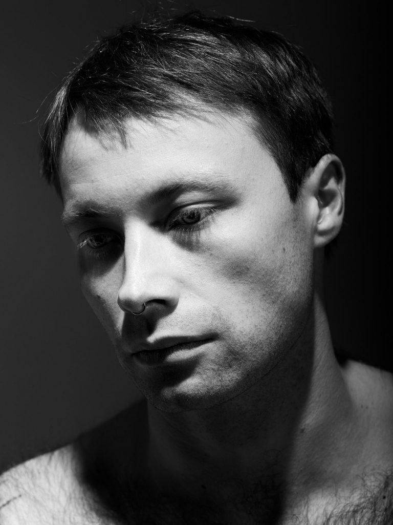 Das Porträt eines jungen Mannes. Die rechte Gesichtshälfte des Mannes liegt im Schatten.