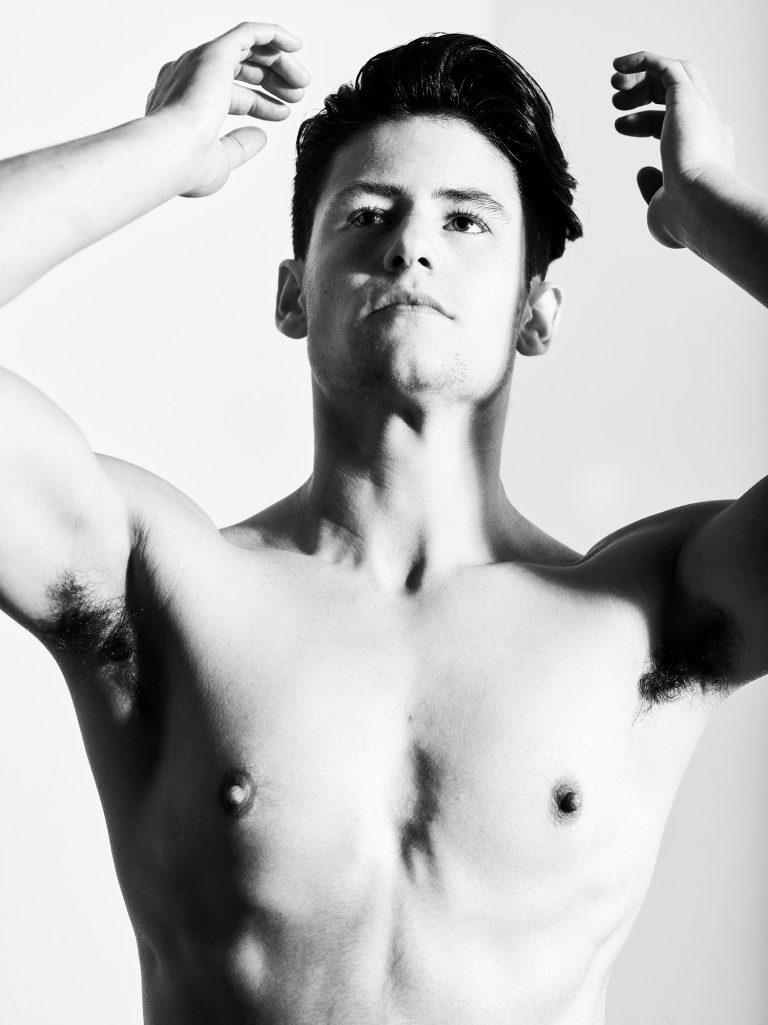 Ein junger Mann mit nacktem Oberkörper streckt beide Hände in die Luft.