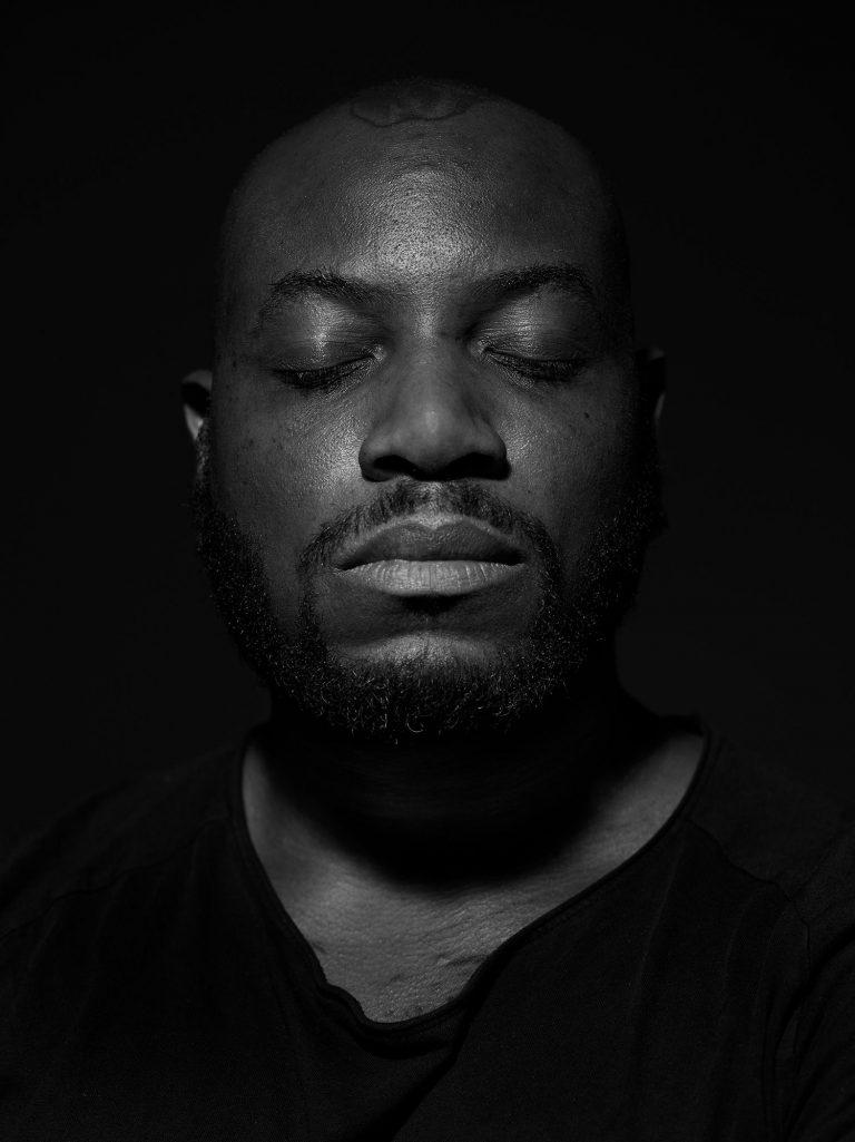 Ein dunkelhäutiger Mann steht mit geschlossenen Augen vor einem dunklen Hintergrund.
