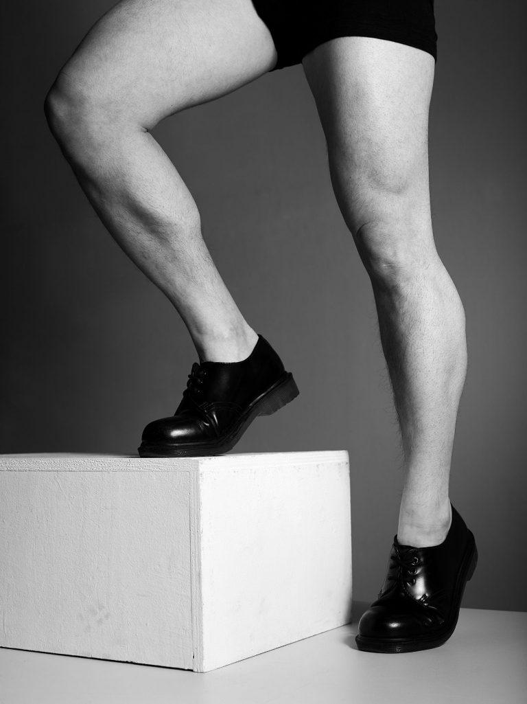 Die nackten Beine eines Mannes. Der Mann trägt Lackschuhe.