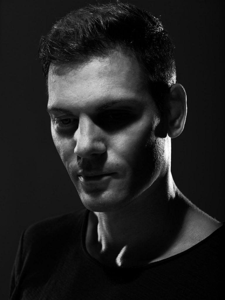 Das Porträt eines jungen Mannes. Die linke Gesichtshälfte des Mannes liegt im Schatten.