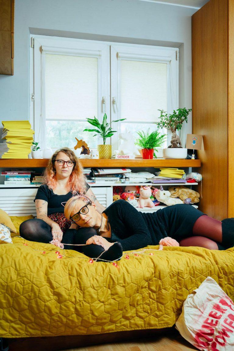 Eine Frau sitzt auf einem Bett. Eine andere Frau liegt neben ihr und legt ihren Kopf in ihren Schoß. Auf dem Boden liegt ein Beutel mit der Aufschrift: Queer Power.