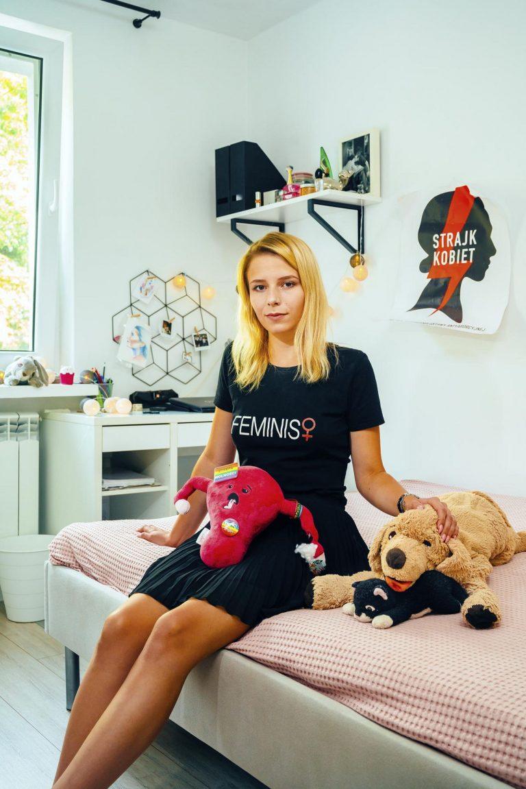 Eine Frau sitzt auf einem Bett. Sie trägt ein T-Shirt mit der Aufschrift: Feminist.
