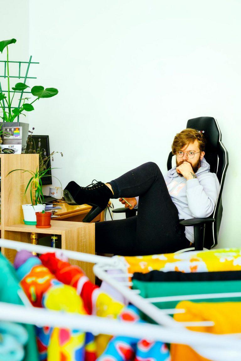 Ein Mann sitzt auf einem Bürostuhl. Er hebt sein Bein. Man kann sehen, dass er Schuhe mit hohen Absätzen trägt.