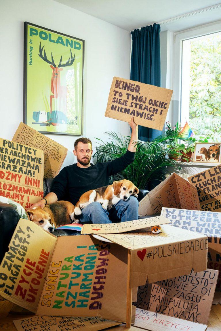 Ein Mann sitzt auf einem Sofa, umgeben von Spruchplakaten. Er hält eins dieser Plakate hoch.