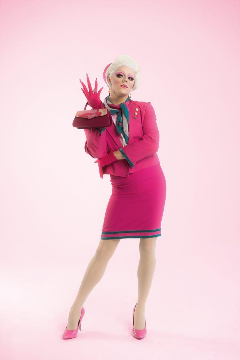 Eine Drag Queen trägt ein pinkes Kostüm, ähnlich dem einer Flugbegleiterin.