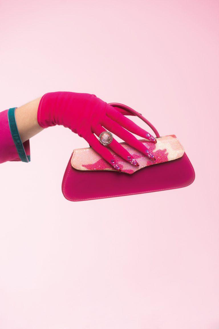 Eine Hand bekleidet mit einem pinken Handschuh hält eine kleine Handtasche fest.