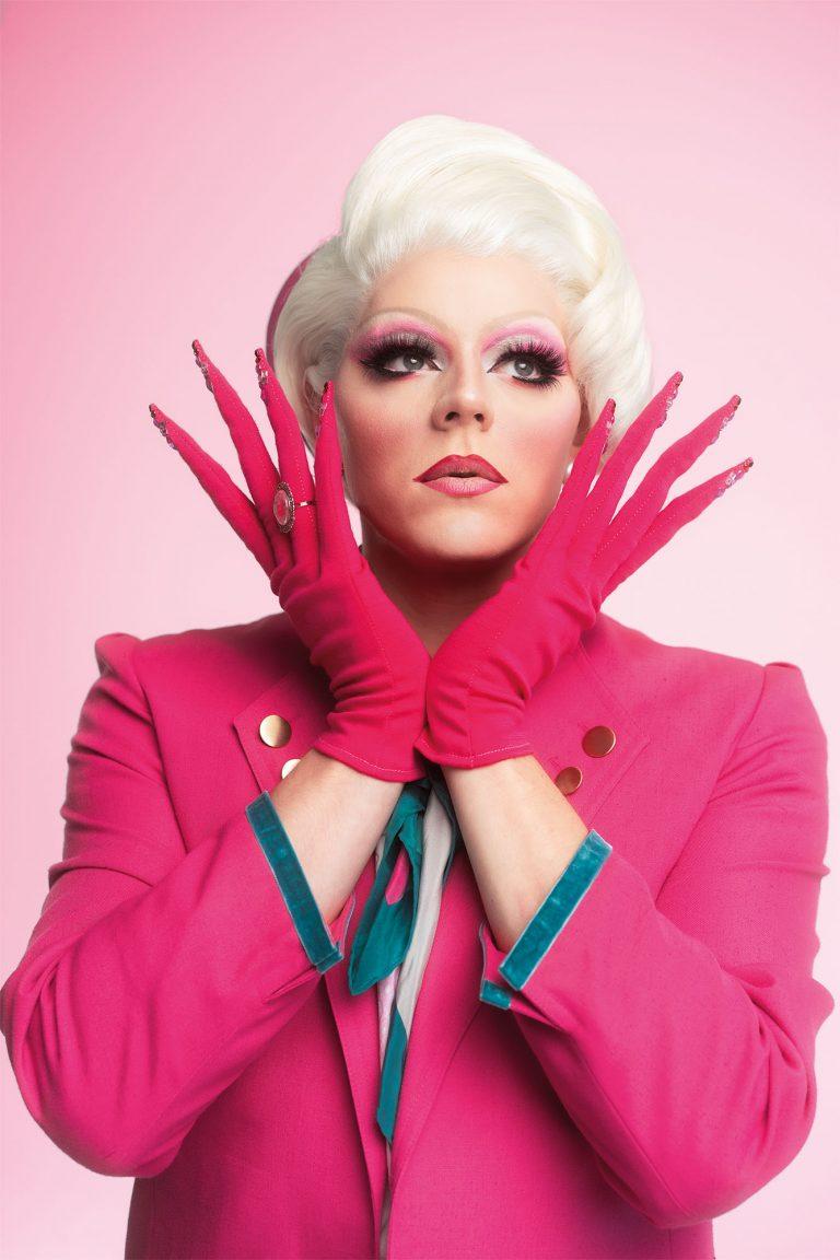 Der Oberkörper der Drag Queen ist zu sehen. Sie hält sich die behandschuhten Hände in V-Form unter das Gesicht.