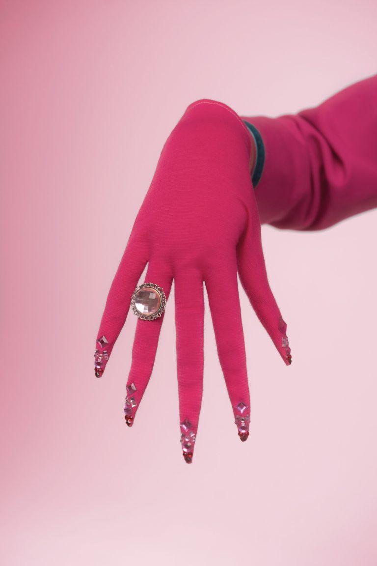 Eine Hand bekleidet mit einem Handschuh wird gezeigt. Am Ringfinger sitzt ein Ring mit großem rosa Stein.