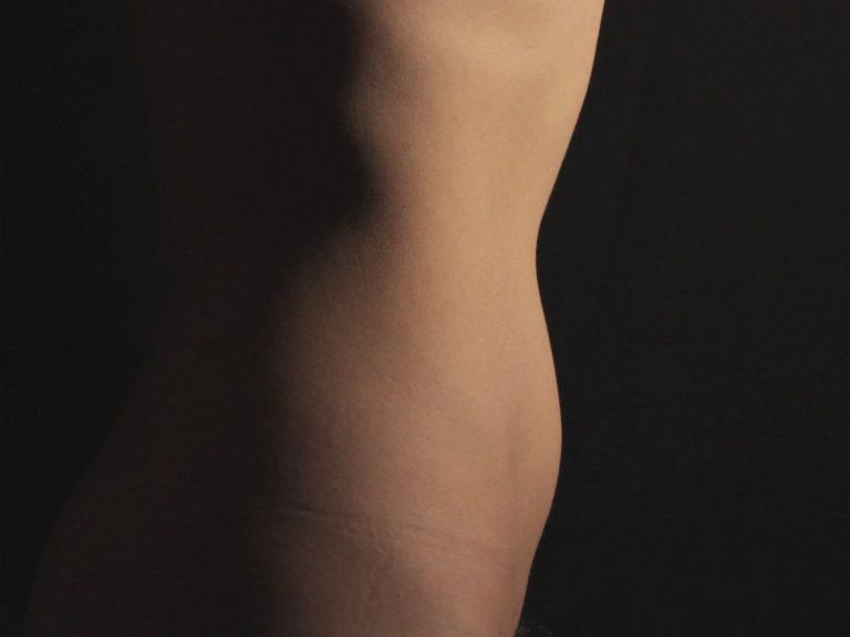 Ein weiblicher Rumpf steht seitlich vor einem schwarzen Hintergrund. Der Bauch wird eingezogen.