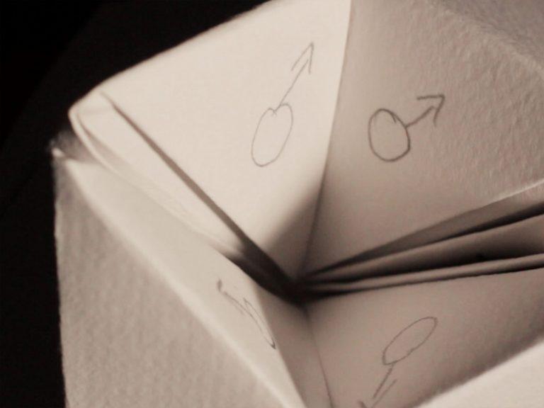 Ein Papierspiel zeigt auf allen vier Seiten das Zeichen für Männlich.