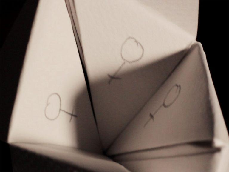 Ein Papierspiel zeigt auf den drei sichtbaren Seiten das Zeichen für Weiblich.