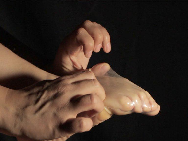 Ein Kondom wird so wie eine Socke über einen Fuß gezogen.