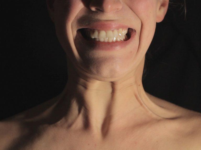 Die untere Hälfte eines weiblichen Gesichts ist zu einem Lächeln verzogen. Am Hals treten sichtbar die Sehnen hervor.