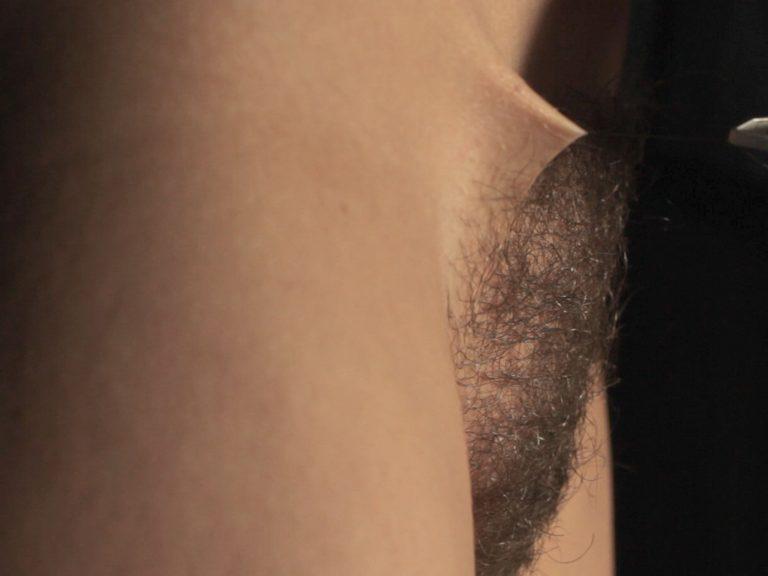 Ein behaarter weiblicher Intimbereich. Ein einzelnes Haar wird mit einer Pinzette herausgezogen.