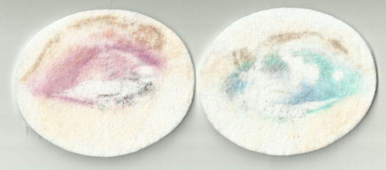 Zwei Wattepads mit den Abdrücken von Augen Make-Up. Das eine Wattepad hat die Farbe pink und das andere grün.