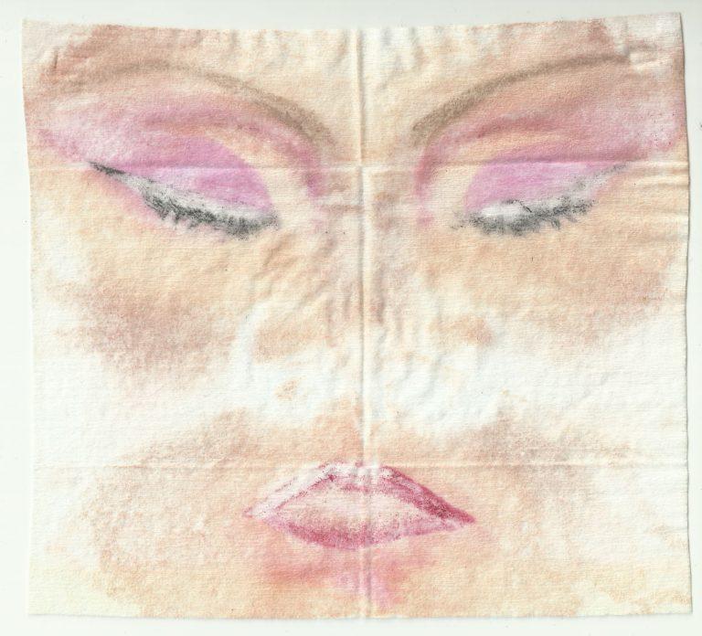 Auf einem Stofftuch ist der Abdruck eines Gesichts Make-Ups zu sehen. Das Augen Make-Up ist pink.