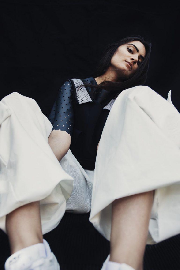 Eine Frau sitzt in der Hocke. Sie trägt eine weite weiße Hose und ein schwarzes T-Shirt mit Löchern.