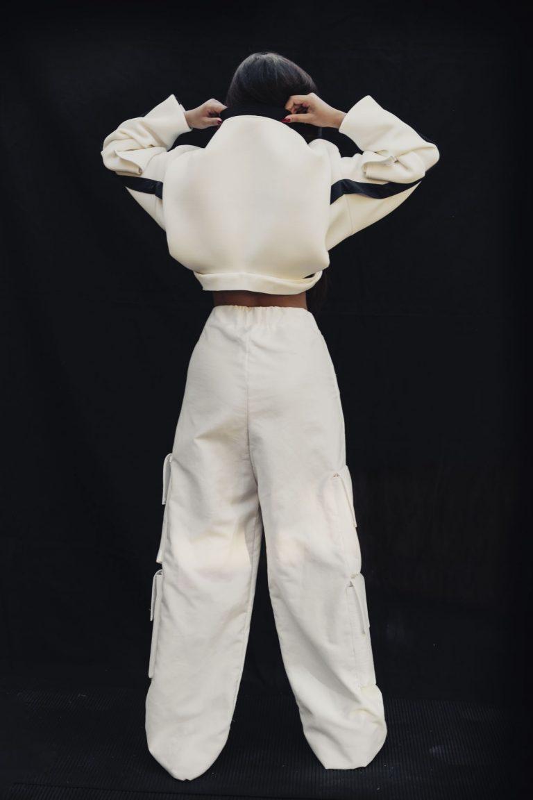 Eine Frau steht mit dem Rücken zum Betrachter. Sie trägt eine weite weiße Hose und einen kurzen weiten weißen Pullover.