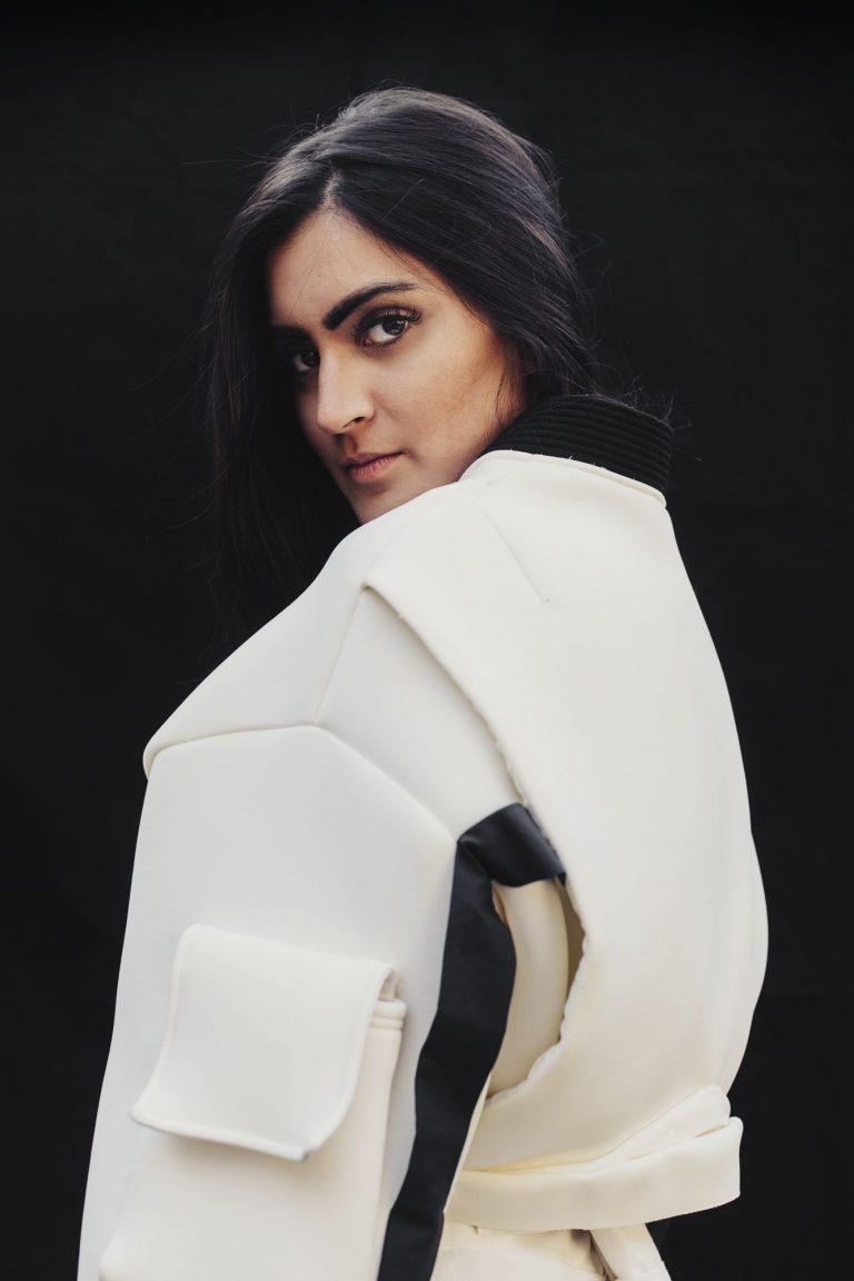 Eine Frau steht seitlich vor einem schwarzen Hintergrund. Sie trägt einen weißen weiten Pullover. Der Pullover hat am Ärmel eine Tasche.