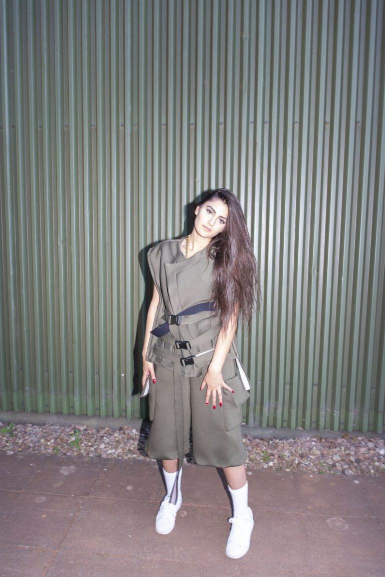 Eine Frau steht vor einer Wellblechwand. Sie trägt einen militärgrünen Zweiteiler mit Schnallen.